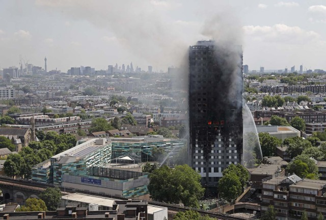Smoke and flames billows from Grenfell Tower as firefighters attempt to control a blaze at a residential block of flats on June 14, 2017 in west London. At least six people were killed Wednesday when a massive fire tore through a London apartment block in the middle of the night, with witnesses reporting terrified people had leapt from the 24-storey tower. / AFP PHOTO / Adrian DENNIS