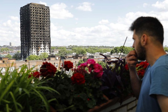 The remains of residential tower block Grenfell Tower are seen from Dixon House a nearby tower block, in west London on June 15, 2017, a day after it was gutted by fire. Firefighters searched for bodies today in a London tower block gutted by a blaze that has already left 12 dead, as questions grew over whether a recent refurbishment contributed to the fire. / AFP PHOTO / Tolga AKMEN