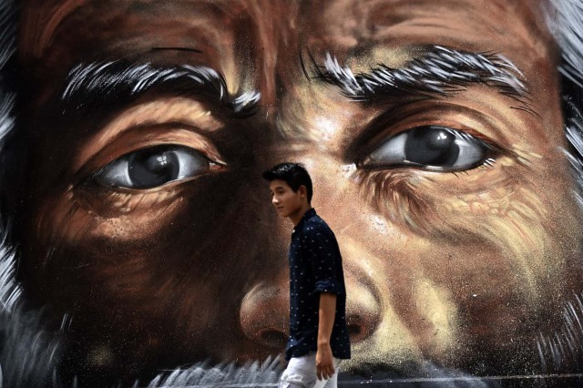 A young man passes by a gratfiti in Cancun, Mexico,  on June 18, 2017. / AFP PHOTO / PEDRO PARDO