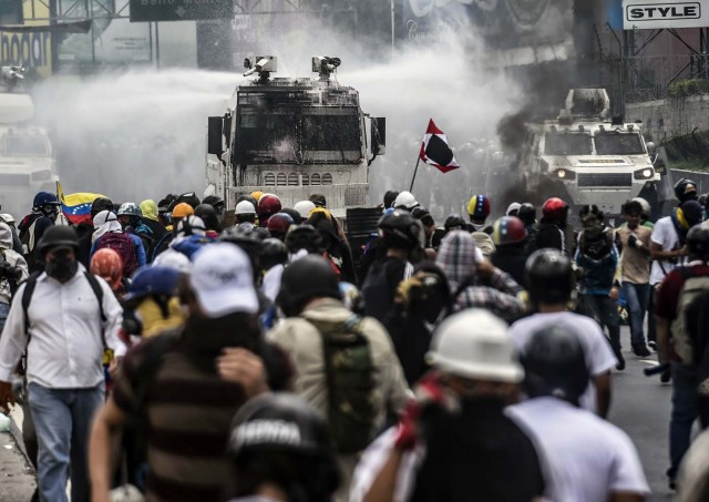 Opposition activists clash with riot police during a demonstration against the government of President Nicolas Maduro along the Francisco Fajardo highway in Caracas on June 19, 2017. Near-daily protests against President Nicolas Maduro began on April 1, with demonstrators demanding his removal and the holding of new elections. The demonstrations have often turned violent with 73 people killed and more than 1,000 injured so far, prosecutors say, and more than 3,000 arrested, according to the NGO Forum Penal. / AFP PHOTO / Juan BARRETO