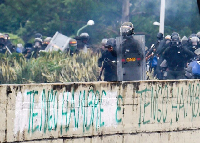 A member of the National Guard holds a gun during clashes with opposition activists demonstrating against the government of President Nicolas Maduro along the Francisco Fajardo highway in Caracas on June 19, 2017. Near-daily protests against President Nicolas Maduro began on April 1, with demonstrators demanding his removal and the holding of new elections. The demonstrations have often turned violent with 73 people killed and more than 1,000 injured so far, prosecutors say, and more than 3,000 arrested, according to the NGO Forum Penal. / AFP PHOTO / Juan BARRETO