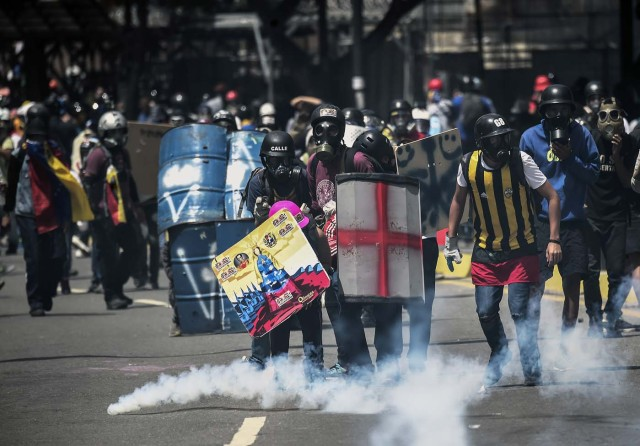 Opposition activists using gas masks and makeshift shields clash with riot police during an anti-government protest in Caracas, on June 22, 2017. / AFP PHOTO / JUAN BARRETO