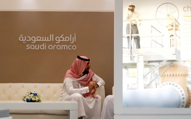 FILE PHOTO: A Saudi Aramco employee sits in the company stand at the Middle East Petrotech 2016, an exhibition and conference for the refining and petrochemical industries, in Manama, Bahrain, September 27, 2016. REUTERS/Hamad I Mohammed/File Photo/File Photo