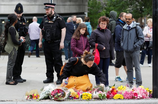 A woman leaves flowers at the south end of London Bridge, near Borough market following an attack which left 7 people dead and dozens of injured in central London, Britain, June 5, 2017. REUTERS/Peter Nicholls