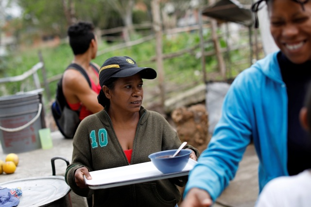 Los partidarios de la oposición que trabajan como voluntarios sirven comida en un comedor para niños, en el barrio La Vega de Caracas, Venezuela, el 23 de mayo de 2017. Foto tomada el 23 de mayo de 2017. REUTERS / Carlos Garcia Rawlins