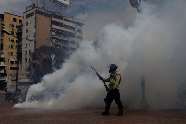 A riot police officer walks near tear gas during a rally against Venezuela's President Nicolas Maduro's government in Caracas, Venezuela June 14, 2017. REUTERS/Carlos Garcia Rawlins