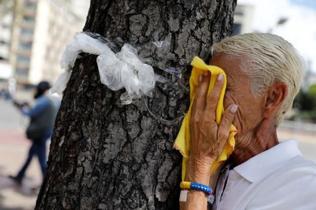 A woman reacts to tear gas during a rally against Venezuela's President Nicolas Maduro's government in Caracas, Venezuela June 14, 2017.  REUTERS/Carlos Garcia Rawlins