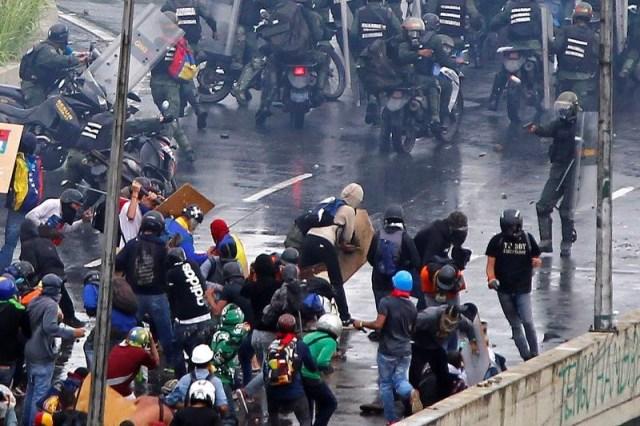Un miembro de las fuerzas de seguridad antidisturbios (derecha) apunta con lo que parece ser una pistola contra un grupo de manifestantes durante una protesta en contra del Gobierno del presidente Nicolás Maduro, en Caracas, Venezuela, 19 de junio de 2017. REUTERS/Christian Veron