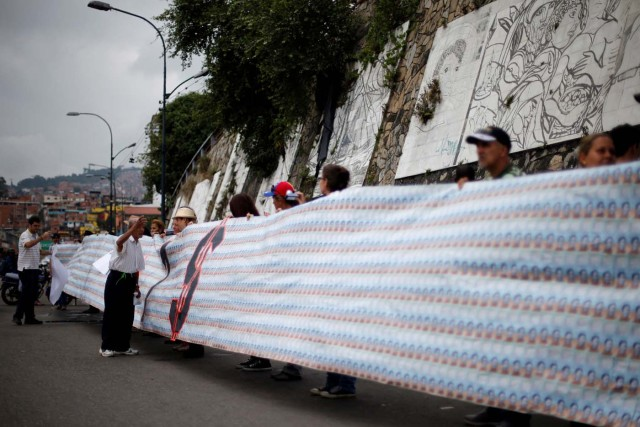 Demonstrators hold a banner made from three thousand two-bolivar-bills, that is equivalent approximately to $1 according to the black market exchange rate, in Caracas, Venezuela, June 10, 2017. Picture taken June 10, 2017. REUTERS/Ivan Alvarado
