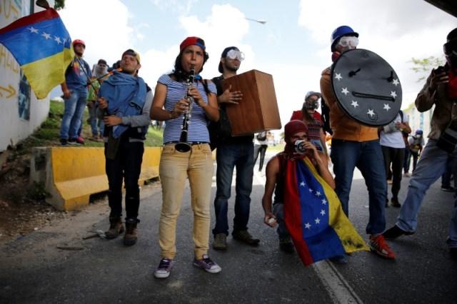 """Manifestantes tocan instrumentos mientras se reúnen en una marcha contra el gobierno de Nicolás Maduro, en Caracas, el 19 de junio de 2017. Unas 20 personas se acuestan y levantan por sorpresa en medio de un transitado bulevar de Caracas y comienzan a recitar algunas frases mientras otros muestran el extracto de un poema escrito con letras de cartón reciclado que dice """"los que matan en realidad no han vivido"""". REUTERS / Ivan Alvarado"""