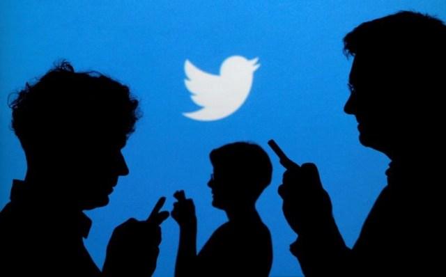 Gente sostiene sus teléfonos móviles tras un fondo en el que se proyecta el logo de Twitter (Foto: Reuters)