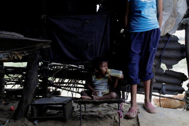 Josue Urdaneta de dos años, quien sufre de desnutrición crónica, toma tetero de agua de arroz porque su madre Aura Urdaneta no consigue leche y cuando consigue no puede comprarla drinks  Paraguaipoa, Venezuela REUTERS/Marco Bello