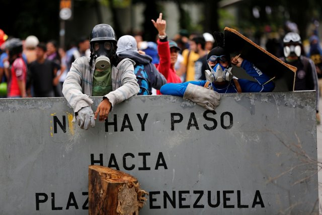 """Opposition supporters stand behind a metal banner they are using to block a street that reads """"blocked road to Venezuela's square"""" during a rally against Venezuela's President Nicolas Maduro's Government in Caracas, Venezuela, June 30, 2017. REUTERS/Ivan Alvarado"""