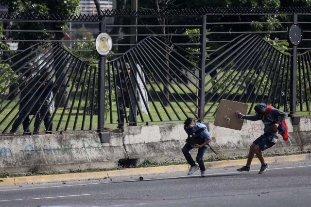 VEN10. CARACAS (VENEZUELA), 22/06/2017.- El joven David José Vallenilla (2d), de 22 años, recibe un disparo de un miembro de la Guardia Nacional Bolivariana (GNB) hoy, jueves 22 de junio de 2017, en las inmediaciones de la bases aérea militar La Carlota, en Caracas (Venezuela). El Ministerio Público (MP) de Venezuela informó hoy del fallecimiento de Vallenilla, que recibió un disparo durante una manifestación opositora en Caracas. Con este deceso la Fiscalía cuenta 75 fallecidos según los datos corregidos y actualizados del organismo en sus informes sobre la oleada de protestas que inició el pasado 1 de abril en el país. EFE/Miguel Gutiérrez