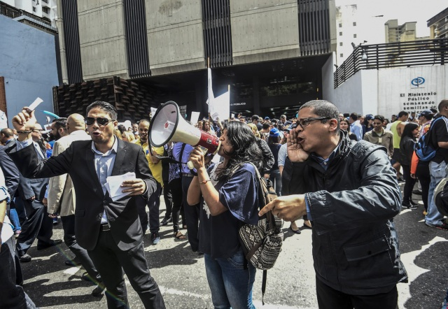 Venezuelan political scientist Necmar Evans (R) joins General Prosecutor's office employees demonstrating in support of Attorney General Luisa Ortega in Caracas on June 19 , 2017.   Venezuela's Supreme Court on Friday rejected a bid to put on trial several senior judges accused of favoring embattled President Nicolas Maduro as he clings to power in the face of deadly unrest. / AFP PHOTO / JUAN BARRETO
