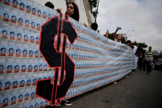 Manifestantes sostienen en Caracas un lienzo hecho con 3.200 billetes de dos bolívares, lo que equivale aproximadamente a un dólar en el mercado negro. 10 de junio de 2017. El tipo de cambio de la última subasta del nuevo sistema cambiario en Venezuela, conocido como Dicom, se mantuvo en 2.640 bolívares por dólar, la misma tasa de la semana anterior, dijo el Banco Central el martes. REUTERS/Iván Alvarado