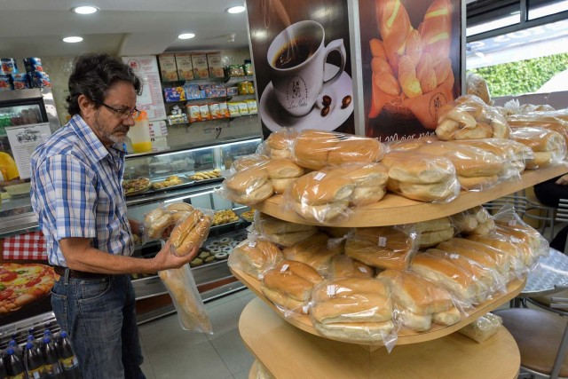 A man buys bread at a bakery, on June 6, 2017 in Caracas, Venezuela. / AFP PHOTO / LUIS ROBAYO / TO GO WITH AFP STORY by ALEXANDER MARTINEZ