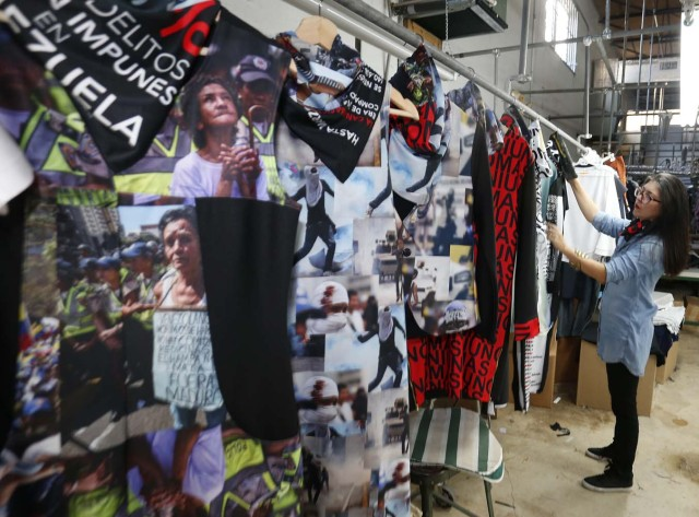 "Venezuelan artist and designer Lisu Vega stands with her collection ""Resistance"" in a warehouse in Miami, Florida on June 8, 2017. The models are dressed in scenes of violence in Caracas and handkerchiefs representing the rags used by protesters to protect themselves from police tear gas. It is the ""Resistance"" collection of Venezuelan fashion designer Lisu Vega. / AFP PHOTO / RHONA WISE"