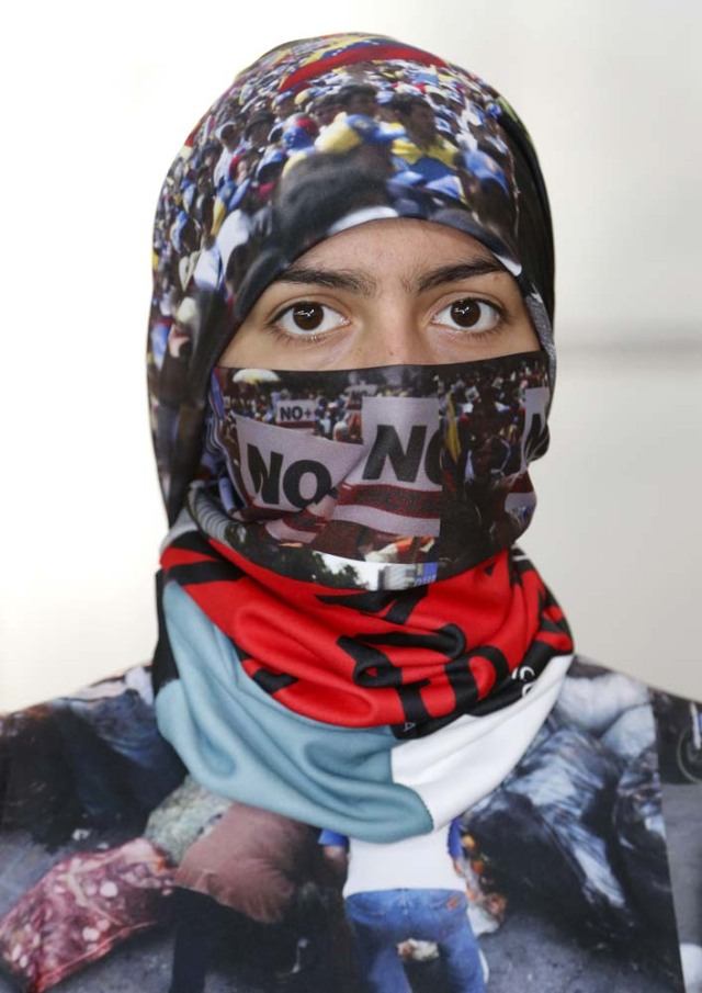 "Vida Delgato models a head scarf by Venezuelan artist and designer Lisu Vega from her collection ""Resistance"" in a warehouse in Miami, Florida on June 8, 2017. The models are dressed in scenes of violence in Caracas and handkerchiefs representing the rags used by protesters to protect themselves from police tear gas. It is the ""Resistance"" collection of Venezuelan fashion designer Lisu Vega. / AFP PHOTO / RHONA WISE"