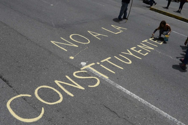 """Venezuelan opposition activists write """"No to the Constituent (Assembly)"""" during an anti-government protest in Caracas on July 10, 2017. Venezuela hit its 100th day of anti-government protests Sunday, amid uncertainty over whether the release from prison a day earlier of prominent political prisoner Leopoldo Lopez might open the way to negotiations to defuse the profound crisis gripping the country. / AFP PHOTO / FEDERICO PARRA"""