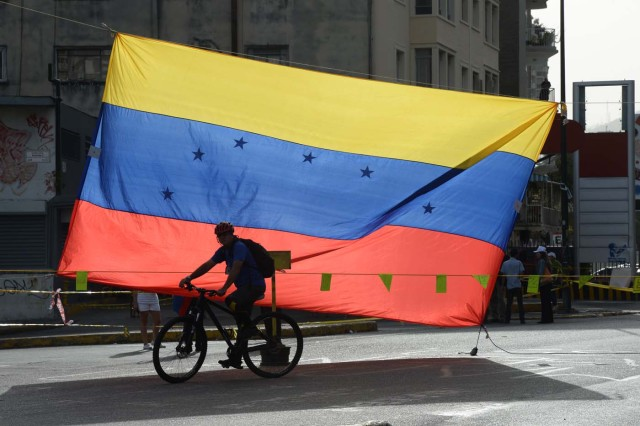A man rides a bicycle in front of a Venezuelan national flag in Caracas on July 10, 2017. Venezuela hit its 100th day of anti-government protests Sunday, amid uncertainty over whether the release from prison a day earlier of prominent political prisoner Leopoldo Lopez might open the way to negotiations to defuse the profound crisis gripping the country. / AFP PHOTO / Federico Parra