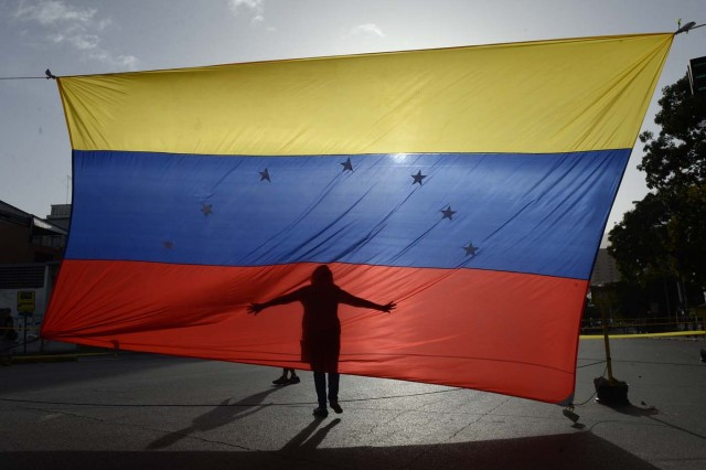 A person's shadow is cast on a Venezuelan national flag in Caracas on July 10, 2017. Venezuela hit its 100th day of anti-government protests Sunday, amid uncertainty over whether the release from prison a day earlier of prominent political prisoner Leopoldo Lopez might open the way to negotiations to defuse the profound crisis gripping the country. / AFP PHOTO / FEDERICO PARRA