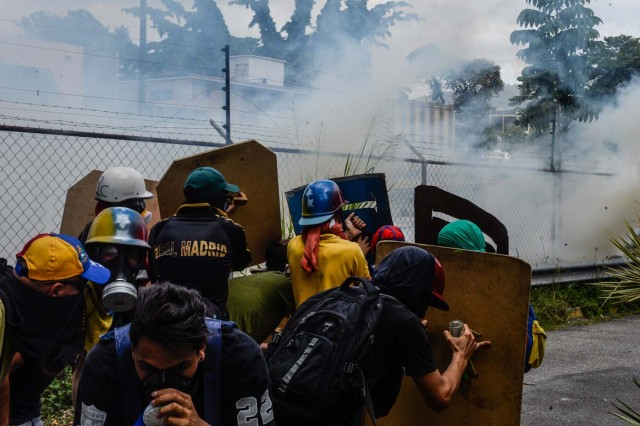 Venezuelan opposition activists clash with riot police during a protest against Venezuelan President Nicolas Maduro in Caracas on July 10, 2017.  Venezuela hit its 100th day of anti-government protests Sunday, amid uncertainty over whether the release from prison a day earlier of prominent political prisoner Leopoldo Lopez might open the way to negotiations to defuse the profound crisis gripping the country. / AFP PHOTO / FEDERICO PARRA