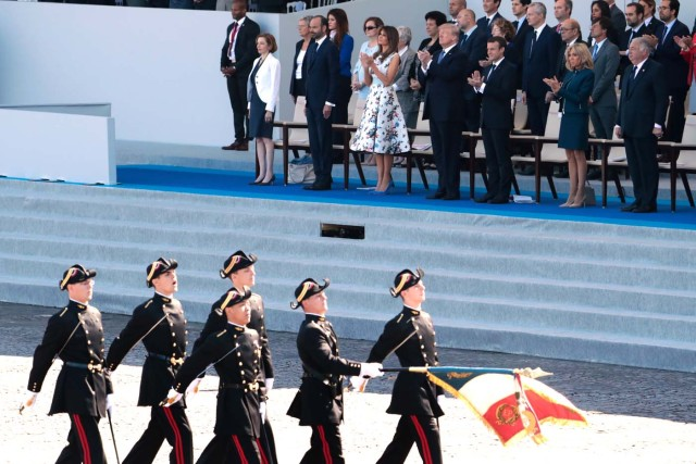 (Bottom row, from R) French President and Senate President Gerard Larcher, wife of French President Brigitte Macron, French President Emmanuel Macron, US President Donald Trump, US First Lady Melania Trump, French Prime Minister Edouard Philippe and French Defence Minister Florence Parly watch as members of the Polytechnic School (Ecole Polytechnique) march during the annual Bastille Day military parade on the Champs-Elysees avenue in Paris on July 14, 2017. The parade on Paris's Champs-Elysees will commemorate the centenary of the US entering WWI and will feature horses, helicopters, planes and troops. / AFP PHOTO / joel SAGET