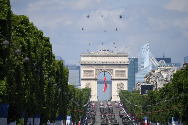 A general view shows troops and helicopters parading during the annual Bastille Day military parade on the Champs-Elysees avenue in Paris on July 14, 2017. The parade on Paris's Champs-Elysees will commemorate the centenary of the US entering WWI and will feature horses, helicopters, planes and troops. / AFP PHOTO / ALAIN JOCARD