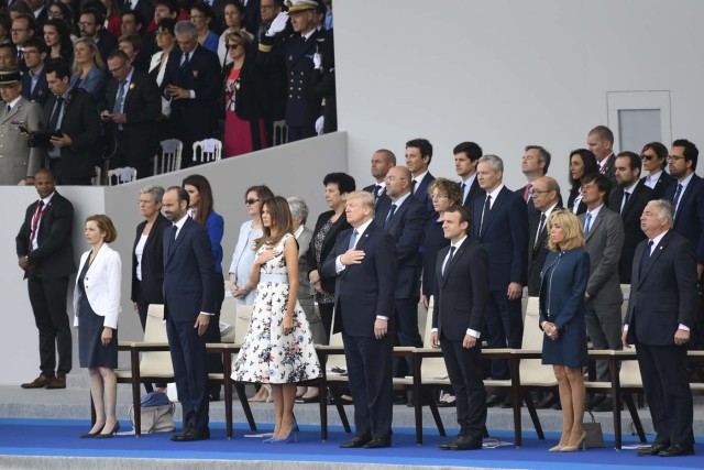 (FromL) French Defence Minister Florence Parly, French Prime Minister Edouard Philippe, US President Donald Trump and his wife First Lady Melania Trump, French President Emmanuel Macron and his wife Brigitte Macron and Senate President Gerard Larcher listen to the US national anthem during the annual Bastille Day military parade on the Champs-Elysees avenue in Paris on July 14, 2017. The parade on Paris's Champs-Elysees will commemorate the centenary of the US entering WWI and will feature horses, helicopters, planes and troops. / AFP PHOTO / SAUL LOEB