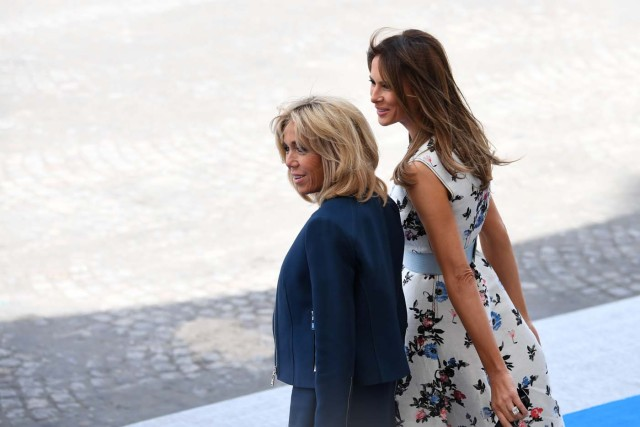 Brigitte Macron, wife of French President, (L) and US First Lady Melania Trump stand during the annual Bastille Day military parade on the Champs-Elysees avenue in Paris on July 14, 2017. The parade on Paris's Champs-Elysees will commemorate the centenary of the US entering WWI and will feature horses, helicopters, planes and troops. / AFP PHOTO / ALAIN JOCARD