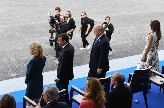 (L-R) Brigitte Macron, wife of French President, French President Emmanuel Macron , US President Donald Trump and US First Lady Melania Trump stand during the annual Bastille Day military parade on the Champs-Elysees avenue in Paris on July 14, 2017. The parade on Paris's Champs-Elysees will commemorate the centenary of the US entering WWI and will feature horses, helicopters, planes and troops. / AFP PHOTO / ALAIN JOCARD