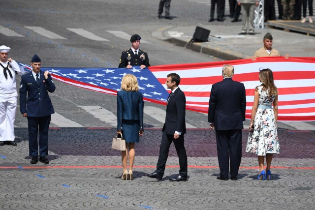 (RtoL) US First Lady Melania Trump, US President Donald Trump, French President Emmanuel Macron and his wife Brigitte Macron, stand in front of the US national flag held by soldiers, at the end of the annual Bastille Day military parade on the Champs-Elysees avenue in Paris on July 14, 2017. The parade on Paris's Champs-Elysees will commemorate the centenary of the US entering WWI and will feature horses, helicopters, planes and troops. / AFP PHOTO / ALAIN JOCARD