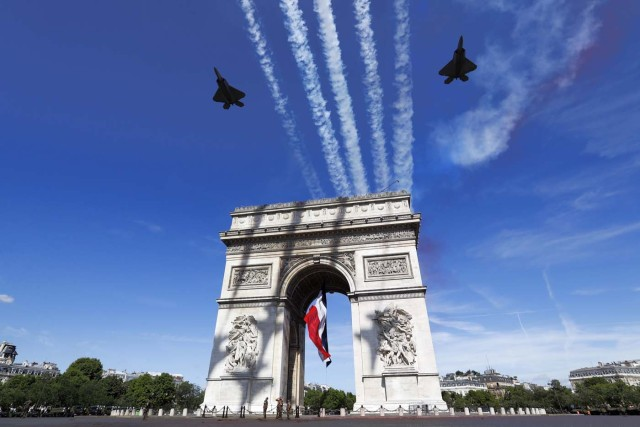 Two F22 of the US Air Force fly over the Arc de Triomphe on the Champs Elysees Avenue in Paris on July 14, 2017, during the Bastille Day military parade.  Bastille Day, the French National Day, is held annually each July 14, to commemorate the storming of the Bastille fortress in 1789. This years parade on Paris's Champs-Elysees will commemorate the centenary of the US entering WWI and will feature horses, helicopters, planes and troops. / AFP PHOTO / POOL / Etienne LAURENT