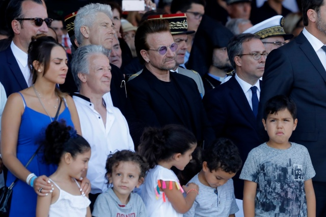 Singer of U2 Bono (C) looks on as he attends a ceremony in Nice, southern France on July 14, 2017, during a one year anniversary commemerations since a jihadist massacre in the Mediterranean city where a man drove a truck into a crowd, killing 86 people.  / AFP PHOTO / POOL / Laurent Cipriani