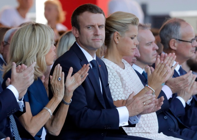 French President Emmanuel Macron (C) looks towards his wife Brigitte Macron during a ceremony in Nice, southern France on July 14, 2017, part of one year anniversary commemerations since a jihadist massacre in the Mediterranean city where a man drove a truck into a crowd, killing 86 people.  / AFP PHOTO / POOL / Laurent Cipriani