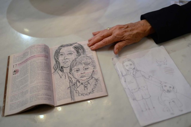 Antonieta Mendoza, mother of Venezuelan opposition leader Leopoldo Lopez, shows drawings made by her son depicting her and his grandson during an interview with AFP in Caracas on July 13, 2017. Lopez, a 46-year-old Harvard-educated politician, was imprisoned for more than three-and-a-half years for allegedly inciting violence by calling for anti-government protests. Today the most prominent opponent of Venezuela's President Nicolas Maduro, spends his first days of house arrest playing with his children, and gradually resumes political activity, holding meetings with international leaders regarding the country's severe crisis.  / AFP PHOTO / FEDERICO PARRA