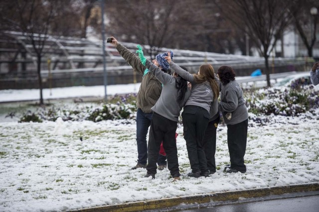 People pose for a selfie during a snowfall in Santiago on July 15, 2017.  An unusual snowfall --the first of such intensity since 2007-- surprised the inhabitants of the Chilean capital, causing a few power cuts and minor traffic jams, in particular in the eastern areas of the capital, the closest to the Andes mountain range. / AFP PHOTO / Martin BERNETTI