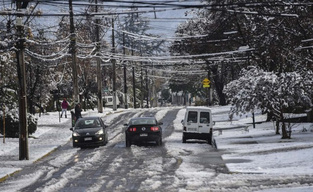 Cars drive along a street covered with snow in Santiago on July 15, 2017.  An unusual snowfall --the first of such intensity since 2007-- surprised the inhabitants of the Chilean capital, causing a few power cuts and minor traffic jams, in particular in the eastern areas of the capital, the closest to the Andes mountain range. / AFP PHOTO / Martin BERNETTI