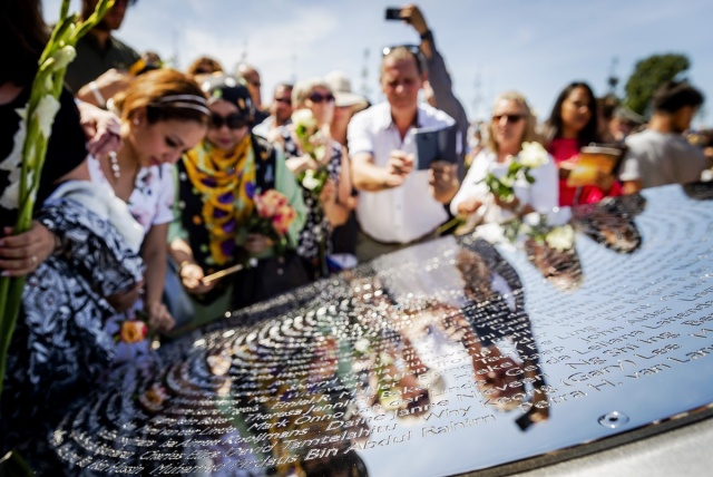 """Relatives attend the unveiling of the National Monument for the MH17 victims in Vijfhuizen, on July 17, 2017.  Three years after Flight MH17 was shot down by a missile over war-torn Ukraine, more than 2,000 relatives gather to unveil a """"living memorial"""" to their loved ones. A total of 298 trees have been planted in the shape of a green ribbon, one for each of the victims who died on board the Malaysia Airlines flight en route from Amsterdam to Kuala Lumpur. The flowers also represent """"the sunflower fields in eastern Ukraine where some parts of the plane wreckage were found"""". / AFP PHOTO / ANP / Remko de Waal / Netherlands OUT"""