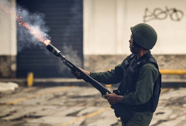 A member of the national guard fires a tear gas grenade at opposition demonstrators during clashes in Caracas on July 28, 2017. Protesters took over streets in Caracas on Friday in a show of defiance to President Nicolas Maduro, as the crisis gripping Venezuela turned deadlier ahead of a controversial weekend election that has earned international scorn. / AFP PHOTO / RONALDO SCHEMIDT