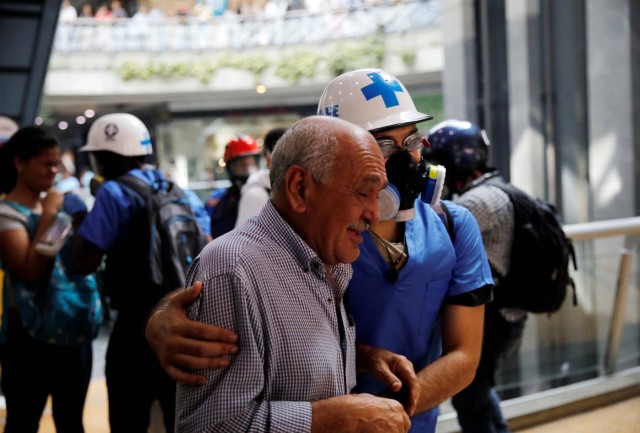 A man is helped as he leaves a shopping mall after smoke from tear gas fired by security forces got inside of it during clashes at a rally against Venezuelan President Nicolas Maduro's government in Caracas, Venezuela, July 6, 2017. REUTERS/Carlos Garcia Rawlins