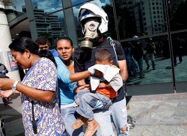 A man carries a child out of a shopping mall after smoke from tear gas fired by security forces got inside of it during clashes at a rally against Venezuelan President Nicolas Maduro's government in Caracas, Venezuela, July 6, 2017. REUTERS/Carlos Garcia Rawlins