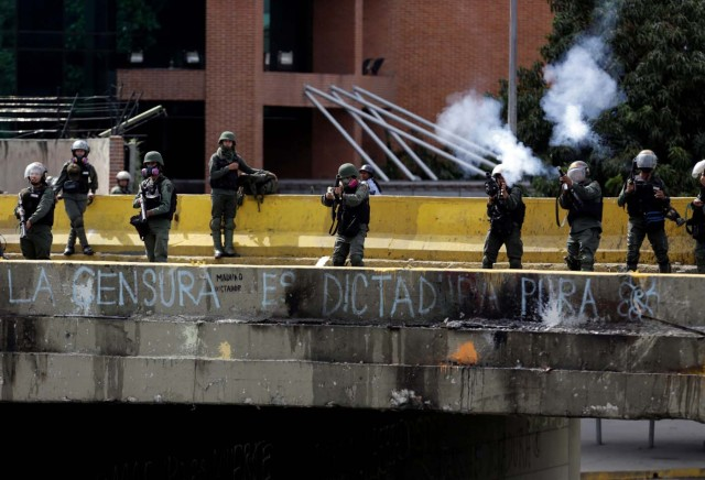 """Security forces fire tear gas during clashes at a rally against Venezuelan President Nicolas Maduro's government in Caracas, Venezuela, July 6, 2017. The grafitti below them reads """"Censorship is pure dictatorship"""". REUTERS/Marco Bello"""