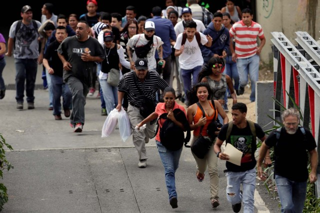 People run during during clashes with security forces at a rally against Venezuelan President Nicolas Maduro's government in Caracas, Venezuela, July 6, 2017. REUTERS/Marco Bello