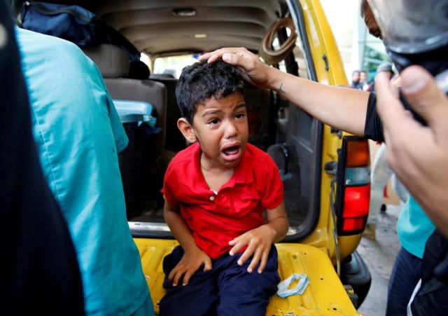 A child cries as he gets medical attention outside a shopping mall after smoke from tear gas fired by security forces got inside of it during clashes at a rally against Venezuelan President Nicolas Maduro's government in Caracas, Venezuela, July 6, 2017. REUTERS/Carlos Garcia Rawlins