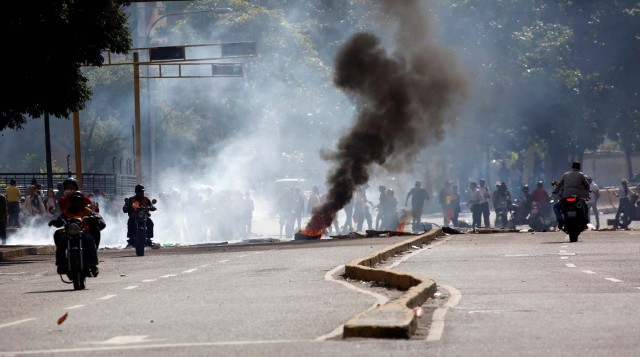 Demonstrators build a barricade as others ride their motorcycles during a rally against Venezuelan President Nicolas Maduro's government in Caracas, Venezuela, July 6, 2017. REUTERS/Carlos Garcia Rawlins