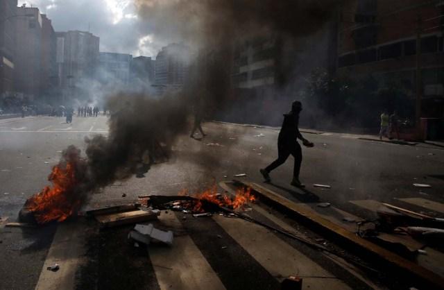 A demonstrator walks by a barricade during a rally against Venezuelan President Nicolas Maduro's government in Caracas, Venezuela, July 6, 2017. REUTERS/Carlos Garcia Rawlins