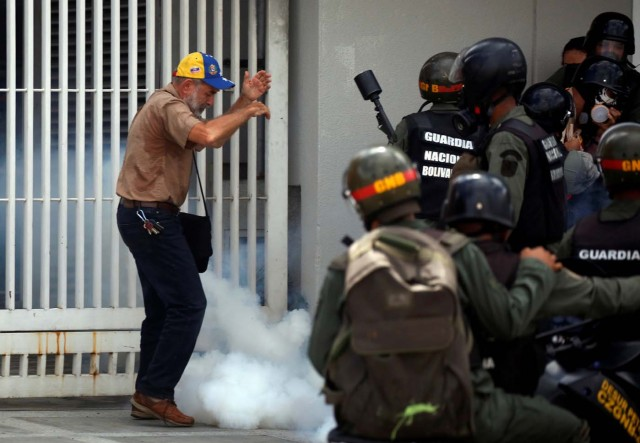 A man stands amidst tear gas smoke as members of the security forces approach him during a rally against Venezuelan President Nicolas Maduro's government in Caracas, Venezuela, July 6, 2017. REUTERS/Carlos Garcia Rawlins