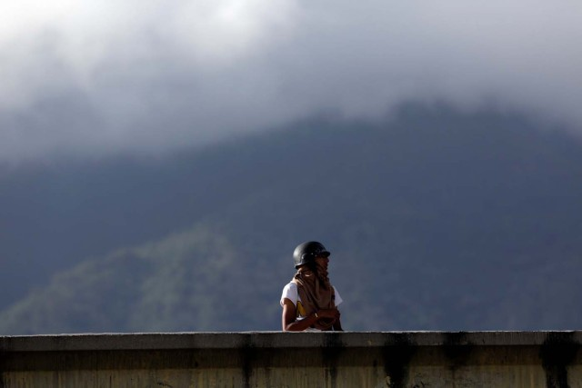 A demonstrator stands on a bridge during clashes with security forces at a rally against Venezuelan President Nicolas Maduro's government in Caracas, Venezuela, July 6, 2017. REUTERS/Marco Bello